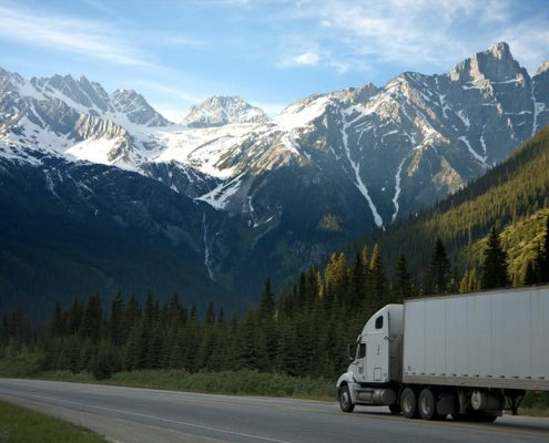 truck driving along road with snowy mountains in background
