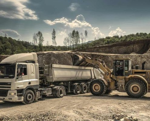 truck being loaded with gravel by front-end loader